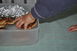 Hand of toddler in a Welsh Cake tupperware container